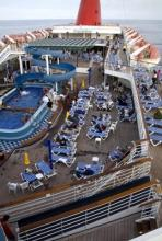 Carnival Paradise Cruise - Pool area - from Wikipedia by Beau Hudspeth